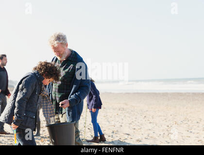 Multi-generation family clam digging on sunny beach - Stock Photo