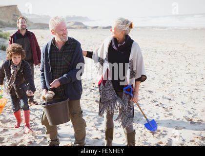 Multi-generation family clam digging on beach - Stock Photo