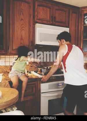 Girl With Father Cooking Food In Kitchen - Stock Photo