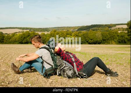 Young hiking couple sitting back to back in field, Great Missenden, Buckinghamshire, U.K - Stock Photo