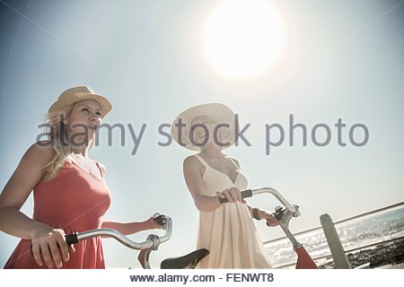 Young women walking with bicycle on seafront - Stock Photo