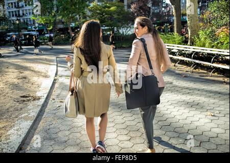 Rear view of young female twins walking through city park - Stock Photo