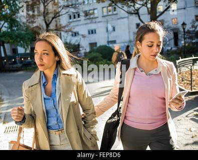 Young adult female twins walking arm in arm through city park - Stock Photo