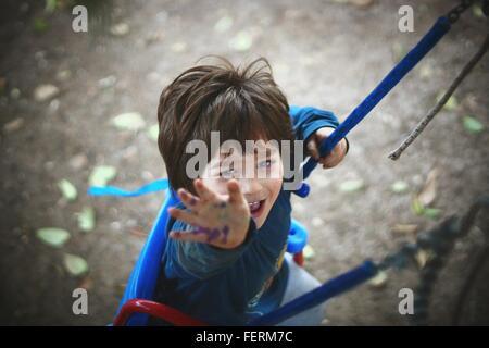 Portrait Of Boy Enjoying Swing In Park - Stock Photo