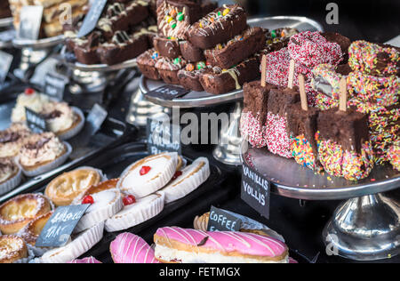 A variety of cakes and chocolate brownies on display in a shop. - Stock Photo