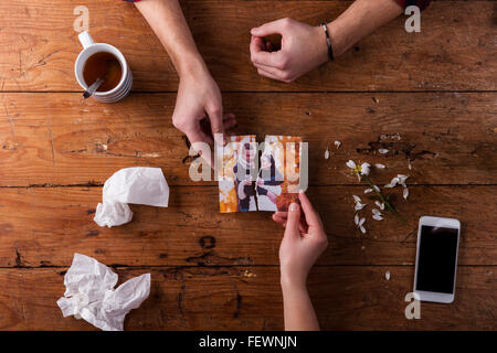 Sad mans, womans hands holding torn picture of romantic couple. - Stock Photo