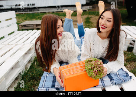Girls lie on the bench and give each other gifts - Stock Photo