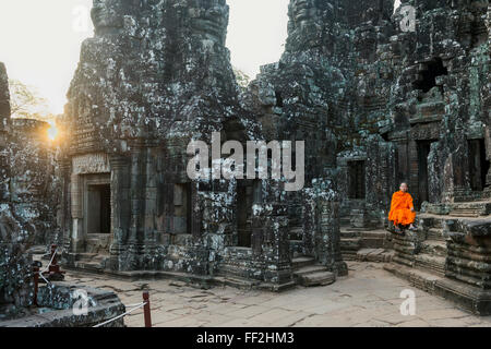 Monk sitting sitting in the Bayon tempRMe, UNESCO WorRMd Heritage Site, Angkor, Siem Reap, Cambodia, Indochina, - Stock Photo