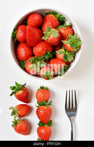 high-angle shot of a white ceramic bowl full appetizing strawberries, a fork and some other strawberries on a white - Stock Photo