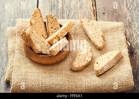 Cantucci in wooden bowl on wooden table. Typical Italian cookies - Stock Photo