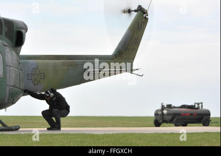 A mechanic from the 54th Helicopter Squadron performs a pre-flight inspection on a UH-1N at Minot Air Force Base, - Stock Photo
