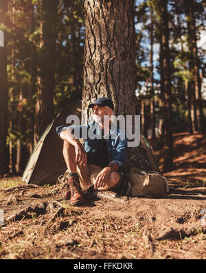 Portrait of senior man sitting alone by a tree with a tent in background. Mature man sitting at a campsite looking - Stock Photo