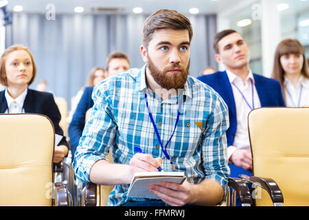 Focused serious young man listening and making notes on presentation in conference hall - Stock Photo