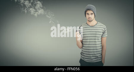 Composite image of portrait of man holding smoking pipe - Stock Photo