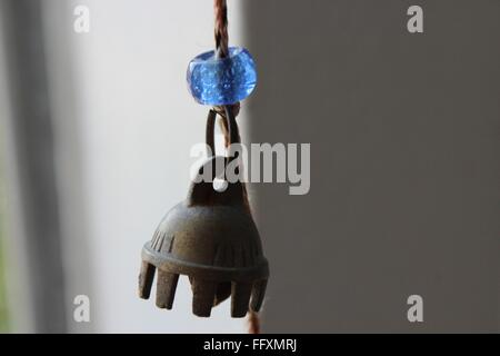 Close-Up Of Wind Chime Hanging Against Wall - Stock Photo