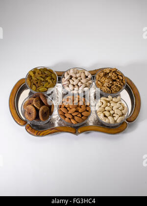 Dry fruits and nuts ; almonds pistachios walnuts raisins figs cashew nuts in bowls on tray - Stock Photo