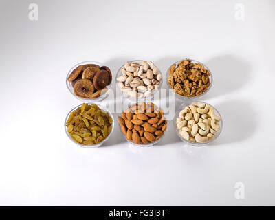 Dryfruit and nut ; almonds raisins cashewnuts figs pistachios walnuts in bowls on white background - Stock Photo