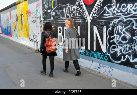 Tourists walking in front of the Berlin Wall at the East Side Gallery, Germany - Stock Photo