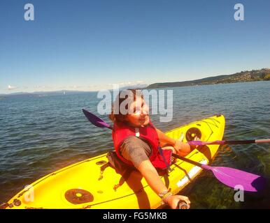 Portrait Of Woman Kayaking In Lake Against Sky - Stock Photo