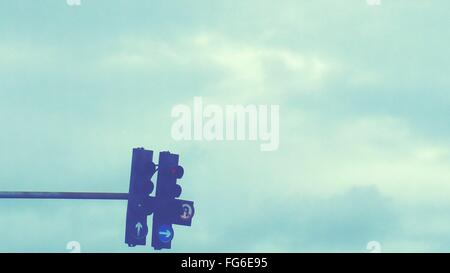 Low Angle View Of Illuminated Road Signal Against Cloudy Sky - Stock Photo