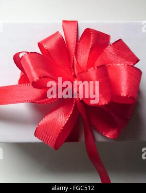 Directly Above View Of Red Bow On Gift Against White Background - Stock Photo