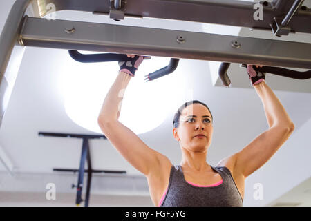 Woman in gym doing arms exercises on a machine - Stock Photo
