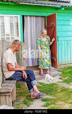 Village landscape. The villagers - mother and son at the entrance in a wooden house. - Stock Photo