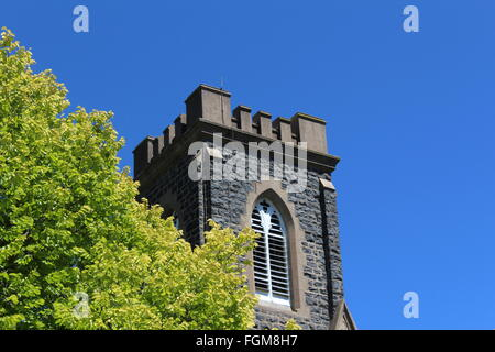 Church steeple against blue sky and next to green leaves - Stock Photo