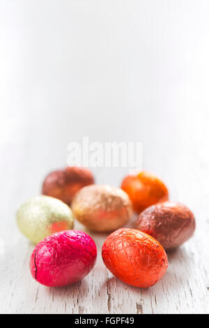 Close up of an assortment of chocolate Easter eggs on a rustic wooden background. - Stock Photo