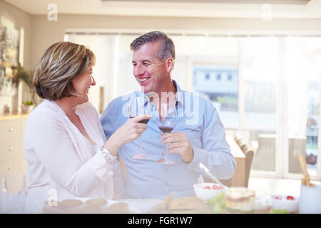Smiling couple toasting red wine glasses in kitchen - Stock Photo