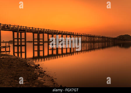 Sunset over the historic wooden U Bein Bridge near Mandalay in Myanmar. Long exposure. - Stock Photo
