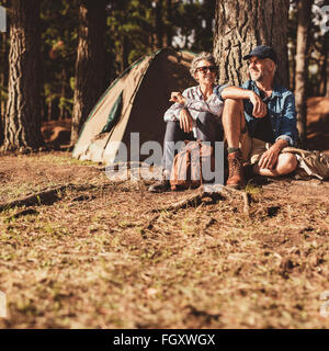 Portrait of happy mature couple sitting together under a tree in forest. Senior man and woman relaxing at their - Stock Photo