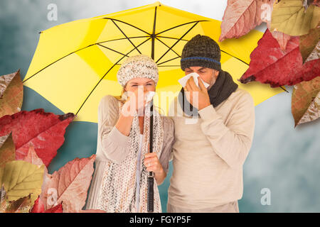 Composite image of couple sneezing in tissue while standing under umbrella - Stock Photo