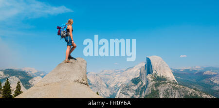 Hiker standing on a cliff, overlooking Half Dome, view from Glacier Point, Yosemite National Park, California, USA - Stock Photo
