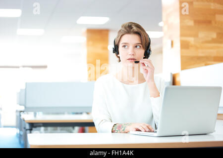 Beautiful young woman in headset sitting and working in call center in office - Stock Photo