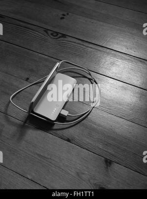 Battery and cellphone on the wooden background - Stock Photo