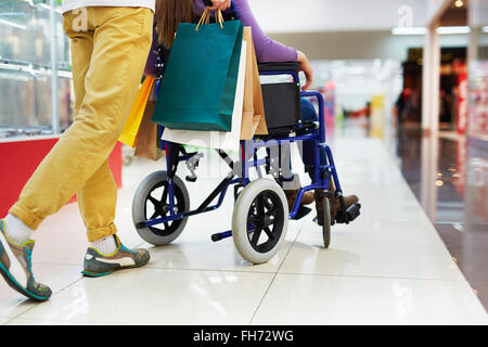 Caring guy helping his girlfriend on wheelchair with shopping - Stock Photo