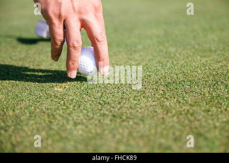 Close up of a hand of a man taking a golf ball - Stock Photo