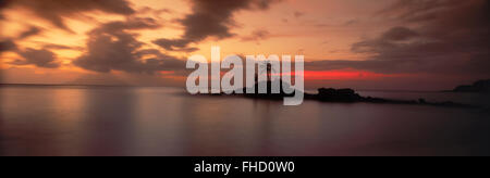 Panoramic photo of couple on rocky point with one palm tree off Mahe Island in Seychelles at sunset - Stock Photo