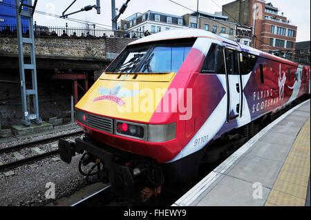 Kings Cross Station, London, UK. 25th February, 2016. Virgin Trains modern day Flying Scotsman liveried train leaves - Stock Photo