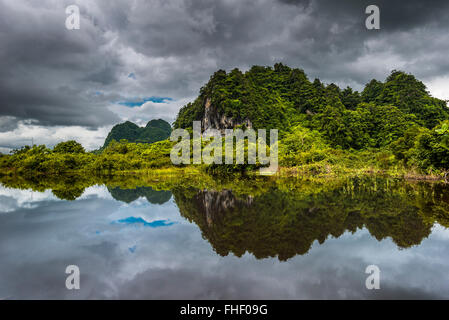 Karst hills with dark clouds, view of the landscape, reflection in the water, near Hpa-an, Karen or Kayin State, - Stock Photo