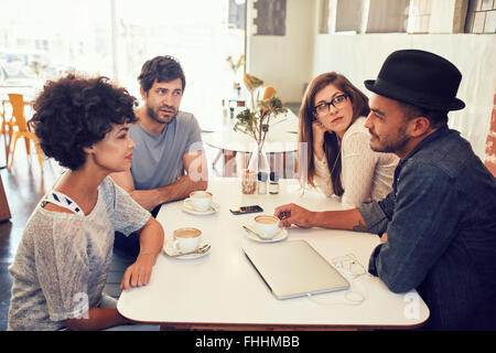 Portrait of young men and women sitting at a cafe table and talking. Group of young friends meeting at a coffee - Stock Photo