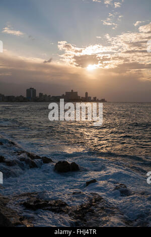 Setting sun sunset over the sea at El Malecon, Havana, Cuba, West Indies, Caribbean, Central America in March - Stock Photo