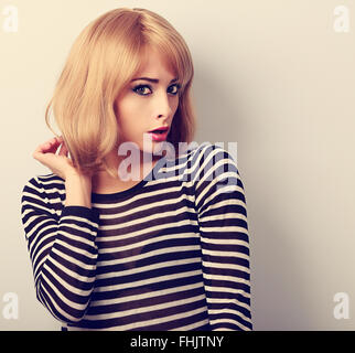 Unhappy blond woman with short hairstyle surprising from bad news. Closeup toned portrait - Stock Photo