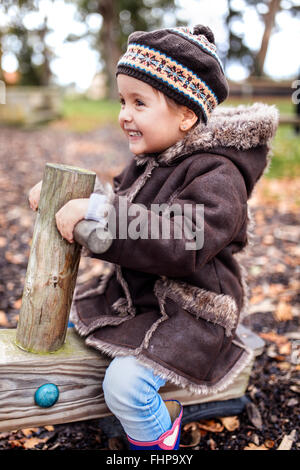 Happy little girl on a playground in autumn - Stock Photo