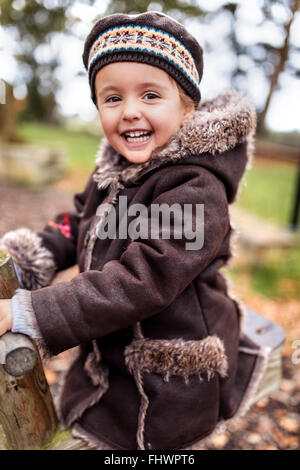 Portrait of happy little girl on a playground in autumn - Stock Photo