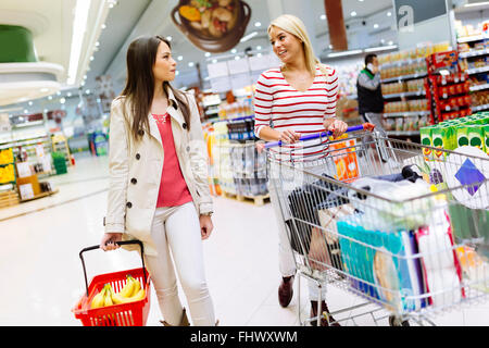 Two beautiful women shopping in supermarket - Stock Photo
