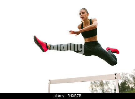 Athlete woman jumping in a running track - Stock Photo