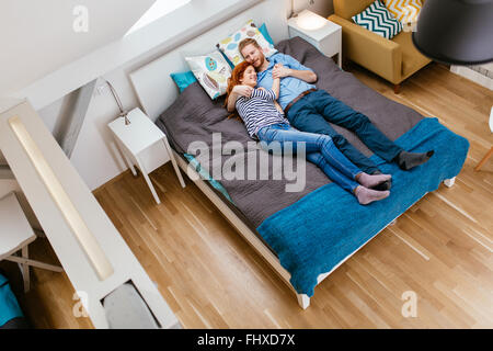 Beautiful couple lying on bed and resting during daytime - Stock Photo