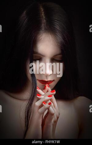sad woman praying in dark - Stock Photo